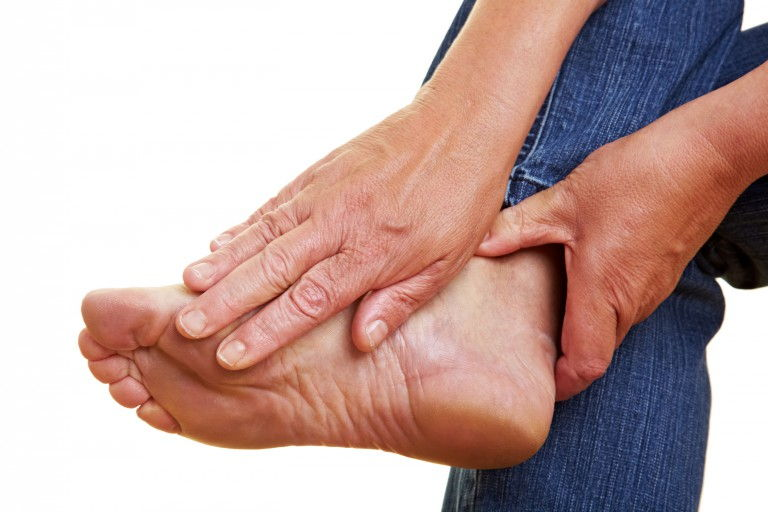 Wrinkled hands touching a naked aching foot